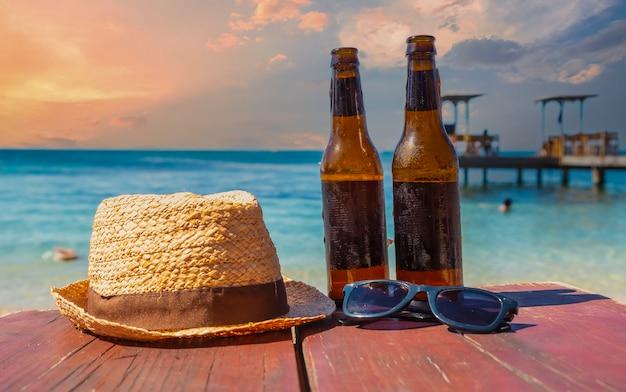 Twee biertjes, zonnebrillen en een hoed op west end beach op roatan island
