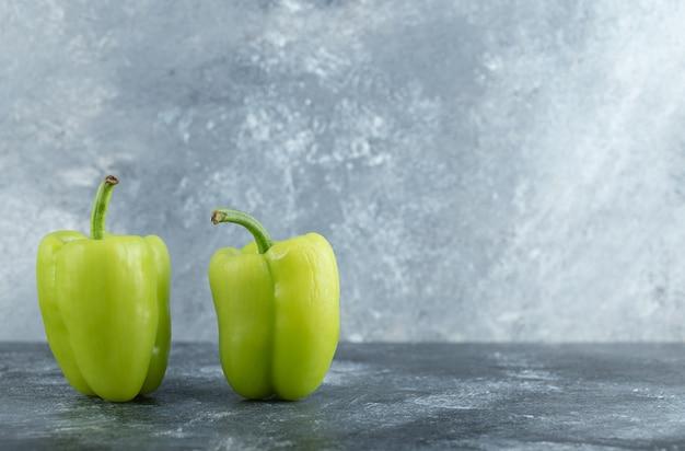 Twee biologische groene paprika's op grijze achtergrond.