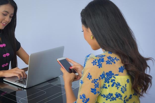 Twee birmese zakenvrouwen plannen werk, met behulp van notebooks en mobiele telefoons die moderne technologie op het werk zijn.