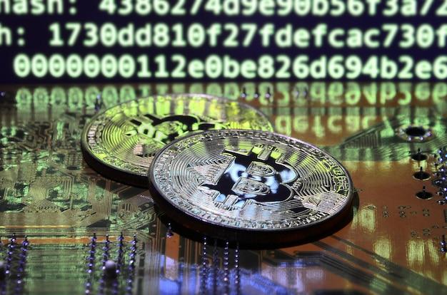 Twee bitcoins liggen op een videokaartoppervlak met achtergrond