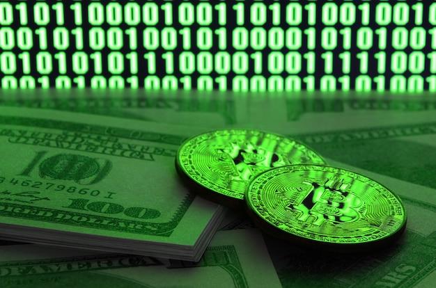 Twee bitcoins ligt op een stapel dollarbiljetten