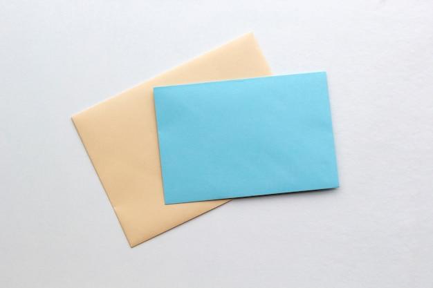Twee blanco papieren enveloppen voor post op wit, plat liggend, bovenaanzicht.