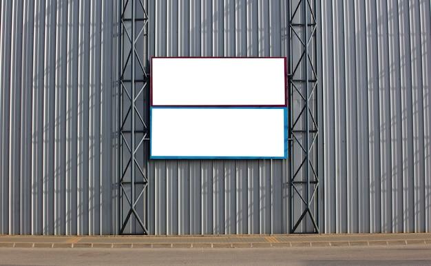 Twee blanco posters geplakt op een metalen muur buiten de gebouwen