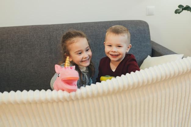 Twee blanke broers en zussen spelen op de bank met een eenhoorn en lachen lief naar de camera