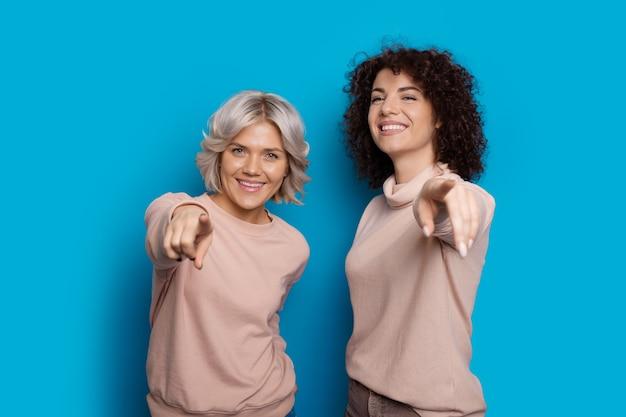 Twee blanke dames met krullend haar wijzen naar de camera en glimlachen gelukkig op een blauwe muur