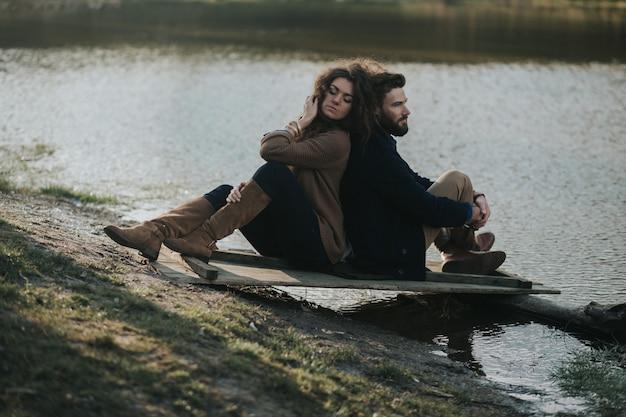 Twee blanke geliefden zittend op de pier bij het meer. een bebaarde man en een gekrulde vrouw verliefd. valentijnsdag.