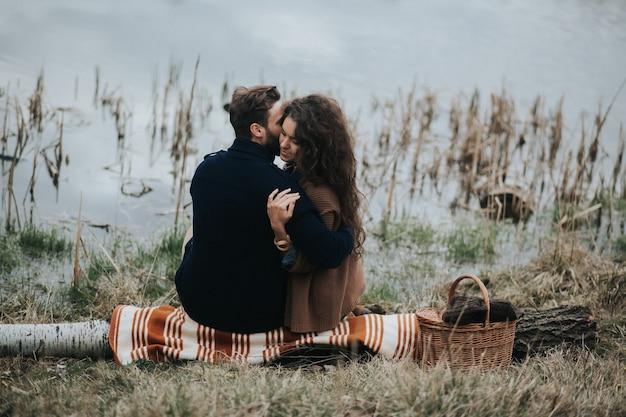 Twee blanke geliefden zittend op een deken aan het meer. jong koppel is knuffelen op herfstdag buitenshuis. valentijnsdag.