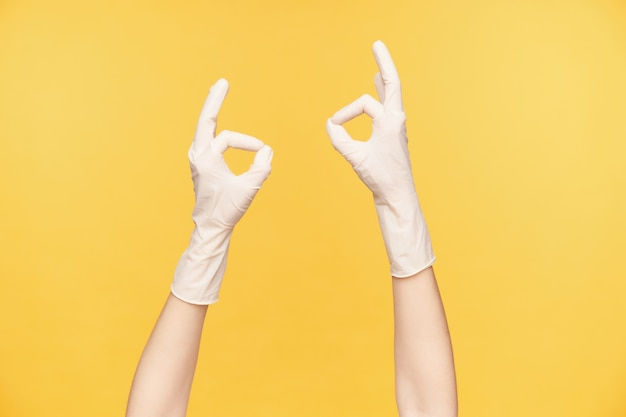 Twee blanke handen in witte rubberen handschoenen vormen ok gebaren met opgeheven handen terwijl wordt geïsoleerd op oranje achtergrond. handen gebaren en tekenen concept