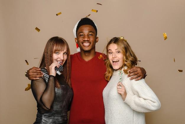 Twee blanke jonge vrouwen blazen een feestelijk deuntje en houden een zuurstok vast en een zwarte man in een kerstmuts lacht en heeft plezier in de studio.
