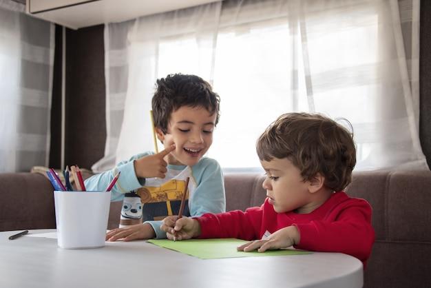 Twee blanke jongen schilderen in caravan tijdens weekendtrip