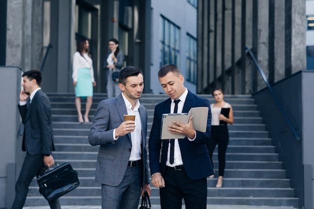 Twee blanke knappe zakenlieden in pakken en stropdassen koffie in handen houden en wandelen van kantoorgebouw na werkdag. stijlvolle mannen praten en zaken bespreken.