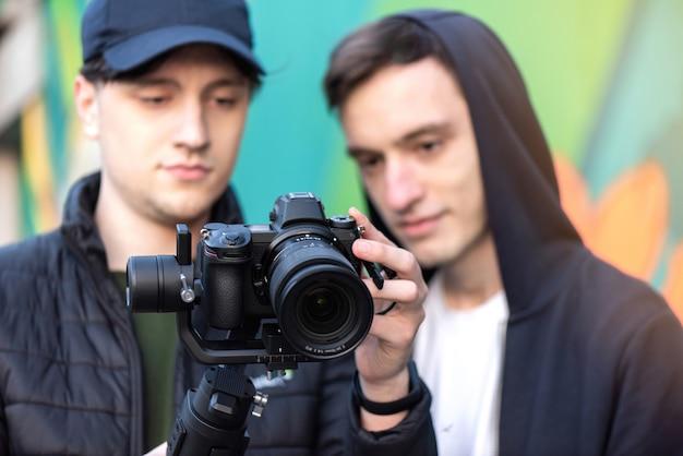 Twee blanke mannen op zoek naar het camerascherm op een steadicam, gekleurde achtergrond