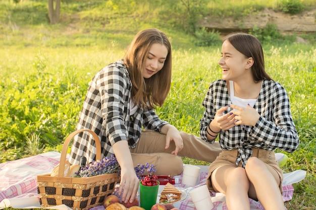 Twee blanke meisjes in het park in de zomer die plezier hebben