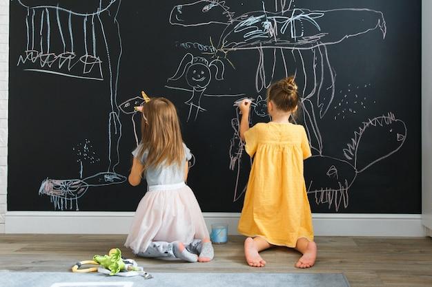 Twee blanke meisjes tekenen op de muur met schoolbord