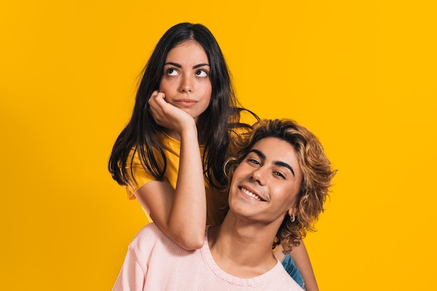 Twee blanke modellen poseren samen voor een gele muur
