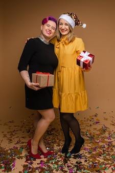 Twee blanke mooie vrouwen zwarte en gele jurken vieren nieuwjaar samen met cadeautjes, foto geïsoleerd op bruine muur