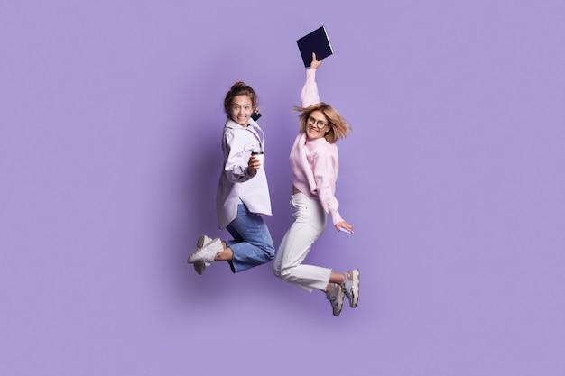 Twee blanke studenten in vrijetijdskleding springen op een violette studiomuur terwijl ze een boek vasthouden en naar de camera glimlachen
