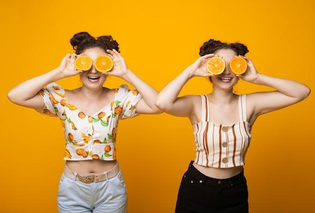 Twee blanke tweelingen die haar oog bedekken met sinaasappels en glimlachen op een gele muur