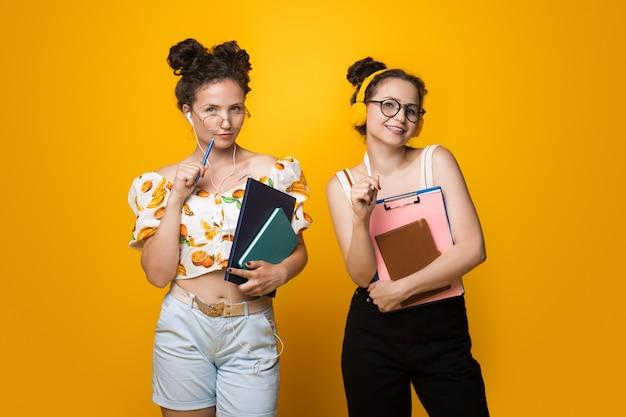Twee blanke universiteitsmeisjes poseren op een gele muur met enkele boeken en mappen die een bril en oortelefoons dragen