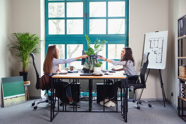 Twee blanke vrouwelijke ontwerpers werken in moderne kantoren. het ene meisje geeft een ander kleurenpalet.