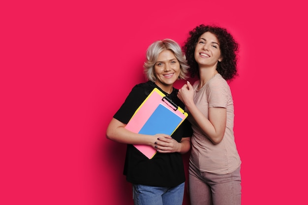 Twee blanke vrouwen met krullend haar poseren op een roze achtergrond glimlachen naar de camera en houden enkele mappen