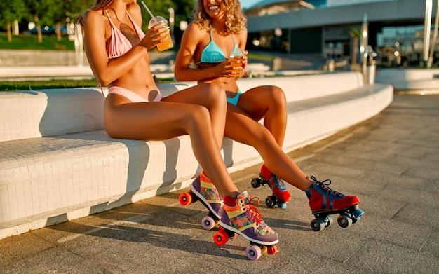 Twee blanke vrouwenvrienden in zwemkleding drinken sap of limonade en skaten dichtbij het strand.