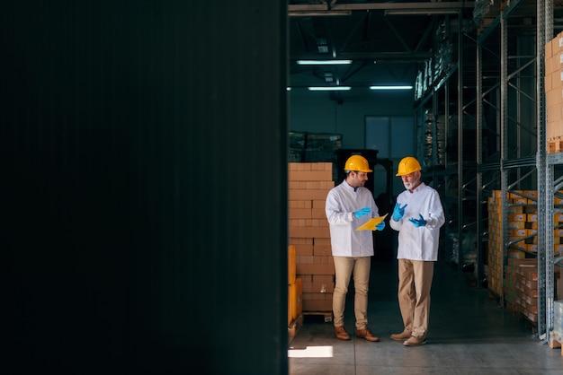 Twee blanke werknemers bespreken terwijl jongere werknemer documenten vasthoudt. magazijn interieur.
