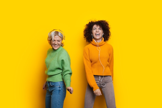 Twee blanke zussen met krullend haar hebben vreugde en dansen op een gele achtergrond met hun koptelefoon