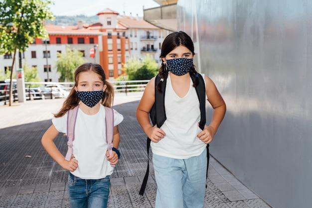 Twee blanke zussen van verschillende leeftijden gaan naar school met maskers op hun gezicht vanwege de coronaviruspandemie covid19