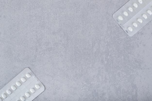 Twee blaren met pillen op een grijze achtergrond.