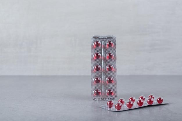 Twee blaren met rode cirkel pillen op grijze achtergrond.