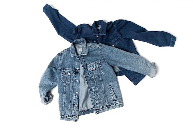 Twee blauw gekleurd jeansjasje dat op wit wordt geïsoleerd