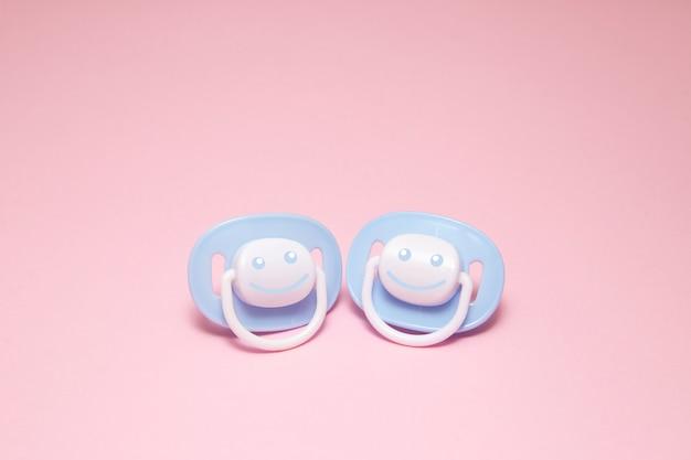 Twee blauwe baby fopspeen of dummy met een glimlach