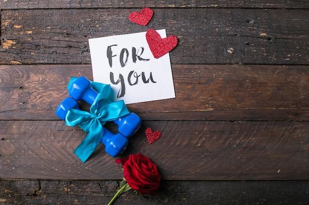 Twee blauwe halter met een cadeau-boog en blanco papier-tag, hart op houten planken, concept van sport vakantie