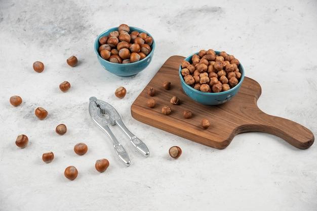 Twee blauwe kommen gepelde hazelnoten en pitten op marmeren tafel.