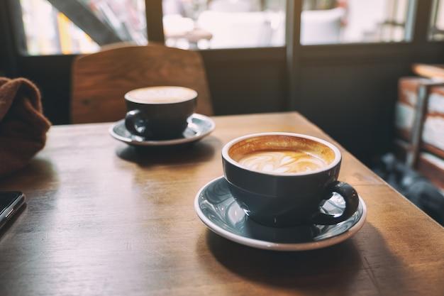 Twee blauwe kopjes hete latte koffie op houten tafel in café