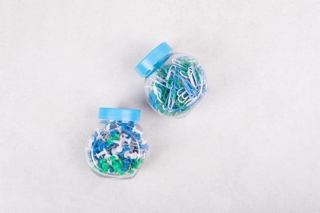 Twee blauwe potten vol kleurrijke pinnen en paperclips op beige achtergrond. hoge kwaliteit foto