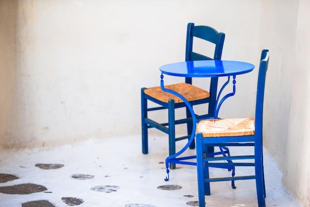 Twee blauwe stoelen op een straat van typisch grieks traditioneel dorp op mykonos-eiland, griekenland, europa