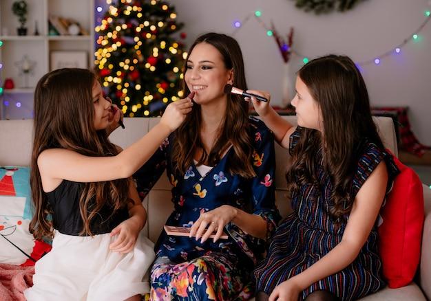 Twee blij zussen en lachende jonge moeder thuis tijdens de kersttijd zittend op de bank in de woonkamer make-up op elkaar zetten kijken elkaar