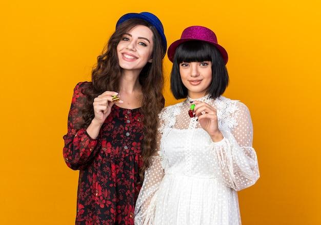 Twee blije feestmeisjes met een feestmuts die allebei een feesthoorn vasthouden en kijken naar de voorkant geïsoleerd op een oranje muur