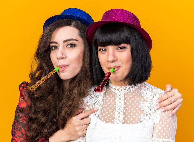 Twee blije feestvrouwen met een feestmuts die beide feesthoorn blazen en kijken naar de voorkant die een ander meisje vasthoudt bij de schouders van achteren geïsoleerd op een oranje muur