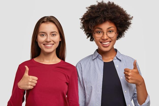 Twee blije gemengde rasvrouwen tonen duim omhoog gebaar met één hand