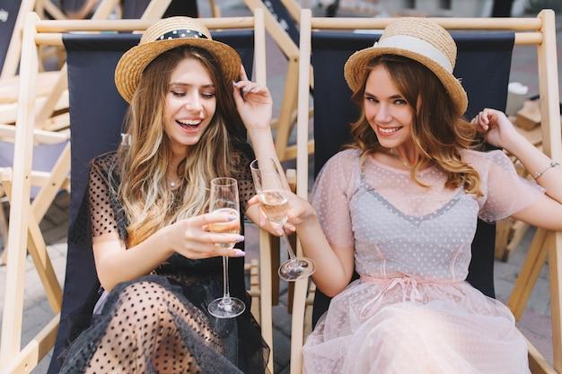 Twee blije meisjes in dezelfde strooien hoeden vieren vakantie met champagne in ligstoelen