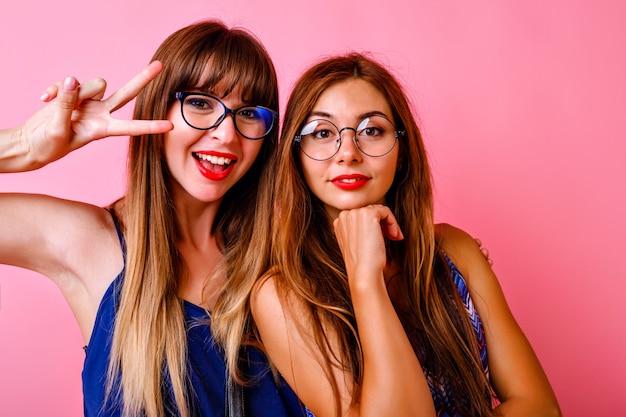 Twee blije vrolijke vrouwen die lachen en plezier hebben op feestje, superpositieve sfeer, blije lachende gezichten, beste hipstervrienden samen, roze muur.