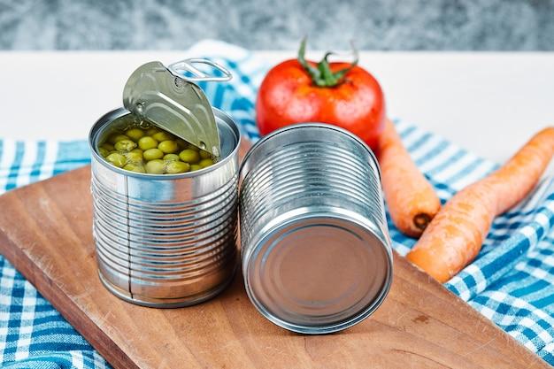 Twee blikjes gekookte groene erwten, groenten en tafelkleed op een witte en marmeren tafel.