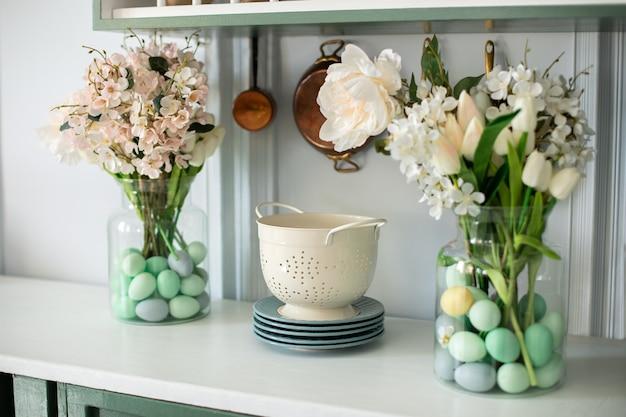 Twee bloemboeketten in glazen vazen met kleurrijke paaseieren erin in de keuken