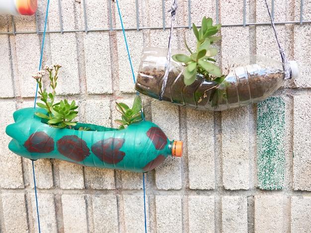 Twee bloempotten gemaakt van plastic flessen, gemaakt door schoolkinderen
