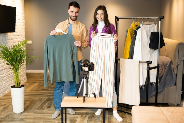 Twee bloggers-influencers maken reclame voor kleding voor online winkels. mooi meisje en jongen filmen een vlog over kleding