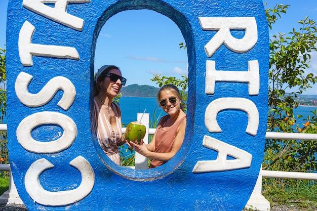 Twee blonde blanke vrouwen poseren in een figuur van een gigantische letter in de zomer