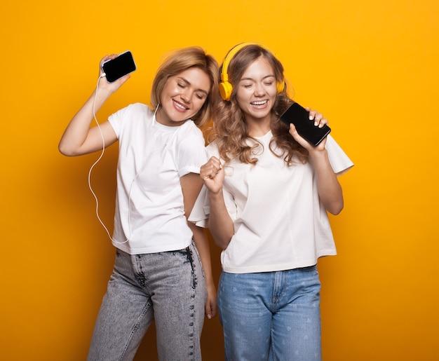 Twee blonde vrouwen luisteren naar muziek met een koptelefoon en mobiel op gele muur